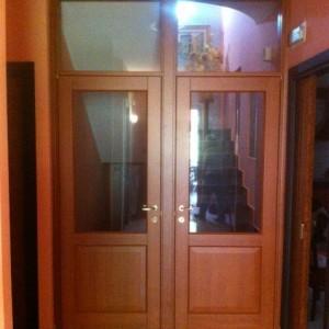 Porte a battenti con vetro e sopraluce della FERRERO LEGNO per chiusura vano scala